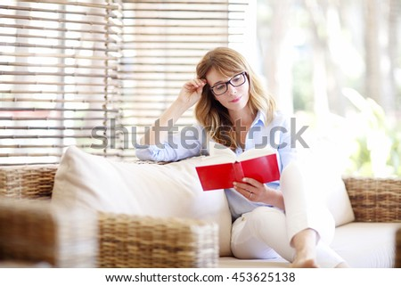 Shot of a pretty middle aged woman sitting on couch and reading book while spending her day at home.