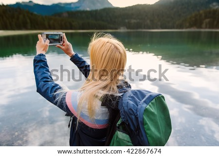 Shot of a pretty young woman getting some shots of the view while hiking - stock photo