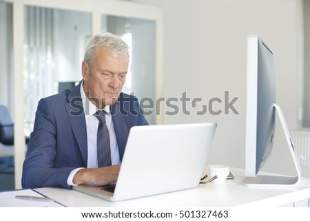Shot of a professional business person working on laptop in his office.