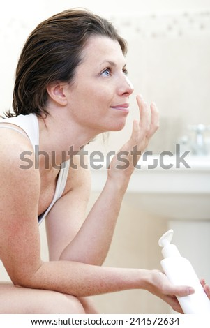 Shot of a 30s Woman Applying Moisturising Cream - stock photo