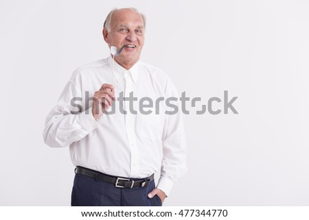 Shot of a senior man holding a paper pipe on a stick while looking at a camera