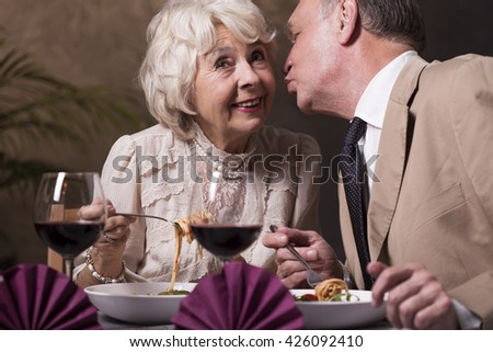 Shot of a senior man kissing his wife on the cheek during a dinner