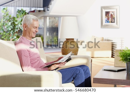Shot of a senior man sitting on couch and reading magazine while relaxing in his modern home.