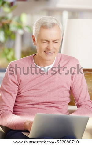 Shot of a senior man using his laptop and working from home while sitting on living room.