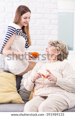 Shot of a senior woman showing her granddaughter how to knit