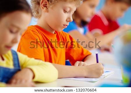 Shot of a serious pupil writing in his copybook - stock photo