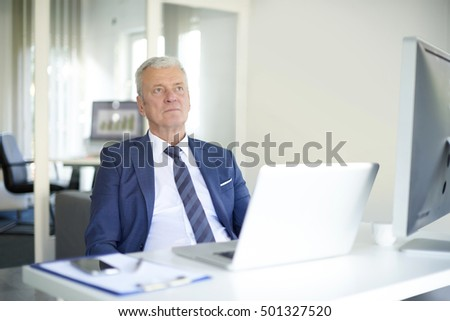 Shot of a serious senior businessman sitting in front of laptop in his office and thinking the solution.