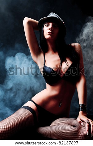 Shot of a sexy woman in black lingerie over dark background with smoke. - stock photo