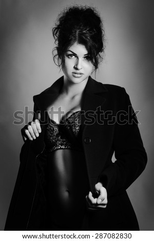 shot of a sexy woman in underwear wearing a large coat  shot in the studio