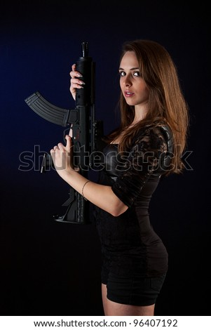 Shot of a sexy woman posing with guns. - stock photo