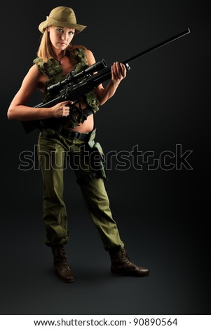 Shot of a sexy woman soldier posing against black background. - stock photo