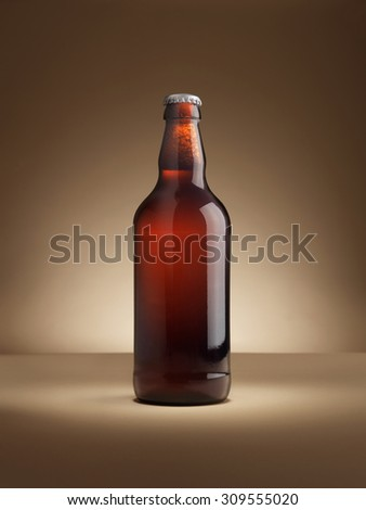 shot of a single bottle of real ale on a coloured background lit with in a halo, vignette style with copy space for the designer. Background is natural, lighting with no post production adjustments.  - stock photo
