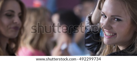 Shot of a smiled woman attending the students' party