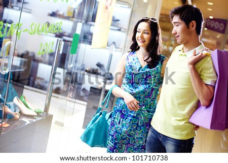 Shot of a smiling couple shopping in the mall - stock photo