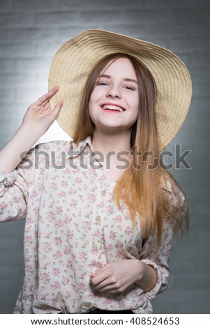 Shot of a smiling young woman wearing a hat