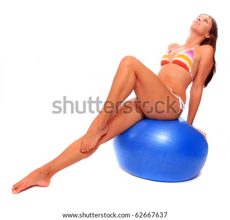 Shot of a sporty young woman dressed in swimsuit sitting on blue ball. Active lifestyle. - stock photo