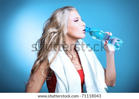 Shot of a sporty young woman drinking water after training. Active lifestyle, wellness. - stock photo