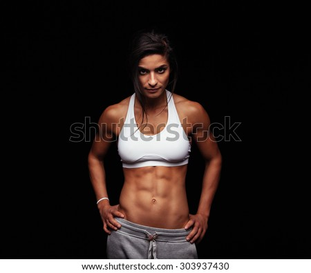 Shot of a strong woman with muscular abdomen in sportswear. Fitness female model posing on black background. - stock photo