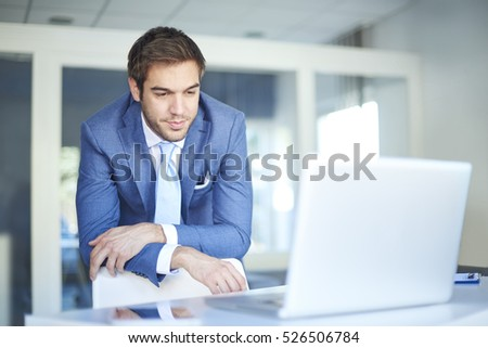 Shot of a thoughtful businessman standing at his workstation.