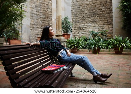 Shot of a thoughtful young female student leaning on a campus bench and resting after classes, beautiful young woman enjoying her leisure time outdoors - stock photo