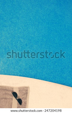 Shot of a Towel and Sunglasses by Pool - stock photo