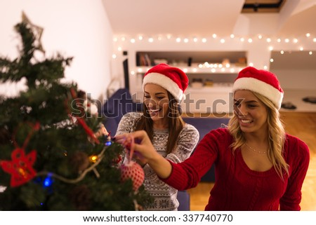 Shot of a two friends decorating a Christmas tree. Selective focus. - stock photo