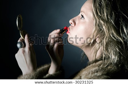 Shot of a Vintage Styled Female Applying her Red Lipstick - stock photo