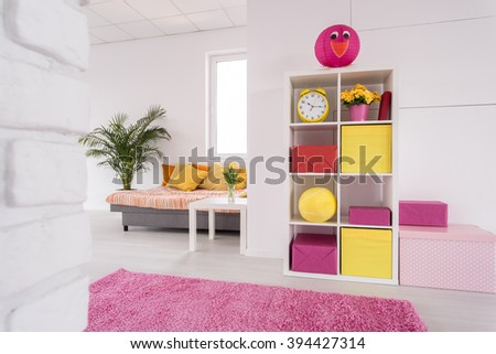 Shot of a white studio apartment with pink and yellow details