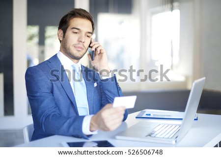 Shot of a young businessman making call and holding bank card while sitting at desk in front of laptop using internet banking.