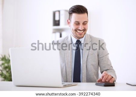 Shot of a young businessman sitting in his office.He is working on his laptop in the office. - stock photo