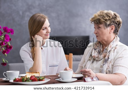 Shot of a young caregiver talking with her senior patient at the table - stock photo
