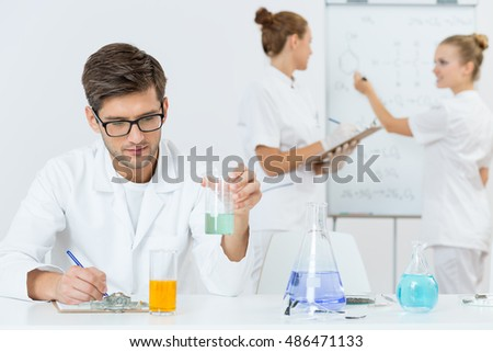 Shot of a young chemist writing notes and his two colleagues discussing a chemical formula in the background