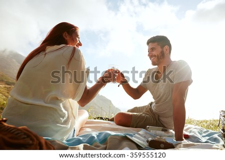 Shot of a young couple drinking wine and enjoying a picnic. Young man and woman toasting wine while sitting outdoors. - stock photo