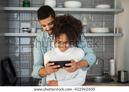 Shot of a young couple relaxing with a tablet in the kitchen.