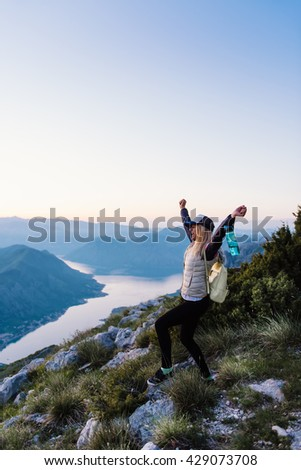 Shot of a young excited woman standing with arms raised in the sky after hiking to mountain top  - stock photo