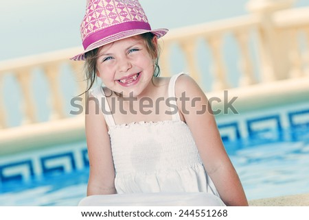 Shot of a Young Girl Sitting by the Pool - stock photo