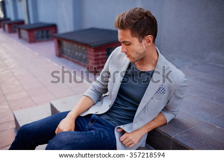 Shot of a young handsome man in suit sitting on a staircase looking aside, fashionable brunette hair man sitting on steps