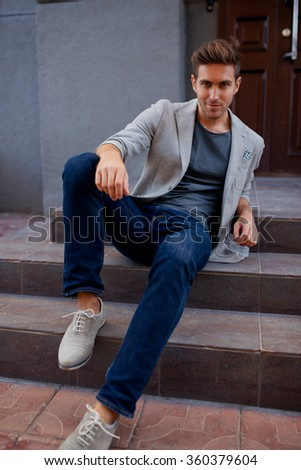Shot of a young handsome man in suit sitting on a staircase looking to the camera, fashionable brunette hair man sitting on steps - stock photo