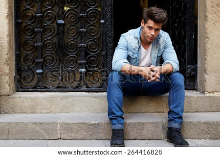 Shot of a young handsome man sitting on a staircase focused looking to the camera, fashionable brunette hair man sitting in a urban setting - stock photo