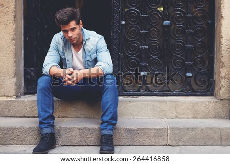 Shot of a young handsome man sitting on a staircase focused looking to the camera, fashionable brunette hair man sitting in a urban setting, filtered image - stock photo