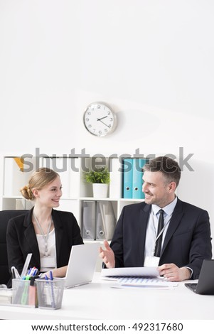 Shot of a young happy businesswoman talking to her colleague