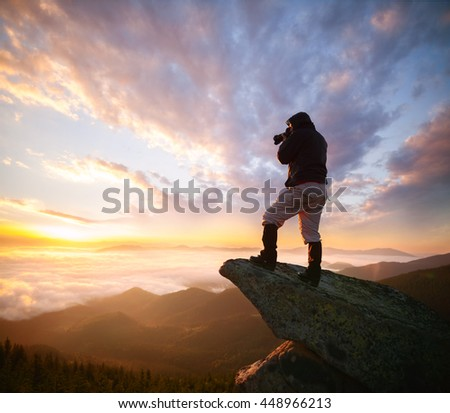 Shot of a young hiker taking photos from the top of a mountain