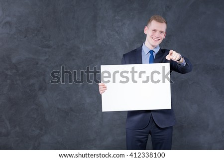 Shot of a young man holding a blank piece of paper and pointing at the camera