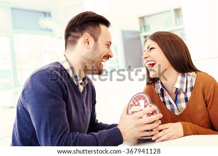 Shot of a young man surprising her girlfriend with a gift.Woman opening a present. - stock photo
