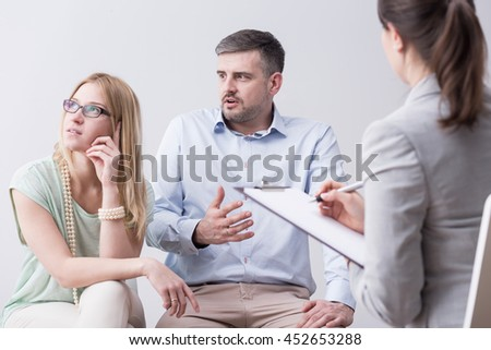 Shot of a young man talking angrily to his resentful wife during a couple's therapy session