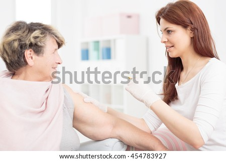 Shot of a young nurse making an injection to a smiling senior woman