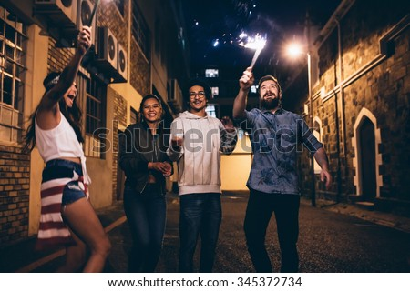 Shot of a young people playing with sparklers at night. Best friends hanging out at night and celebrating 4th of july outdoors. - stock photo