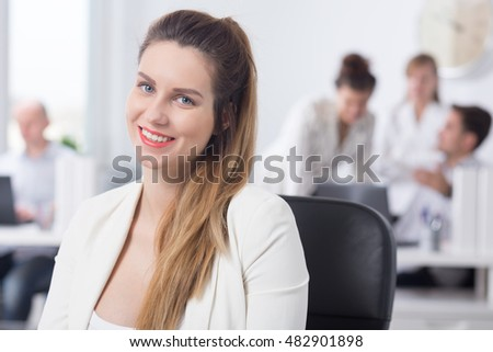 Shot of a young pregnant woman sitting on a chair, working in a light office
