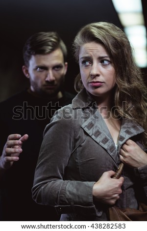 Shot of a young scared woman and a strange man grabbing her arm
