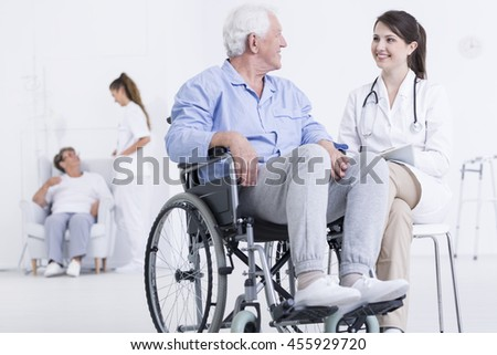 Shot of a young smiling doctor sitting next to her male patient in a wheelchair - stock photo